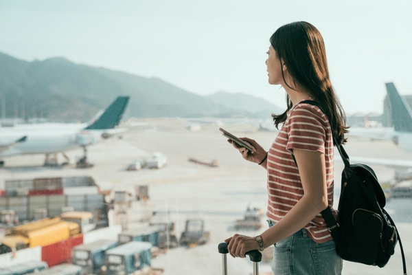 Woman standing in airport watching airplanes on runway, with phone in her hand