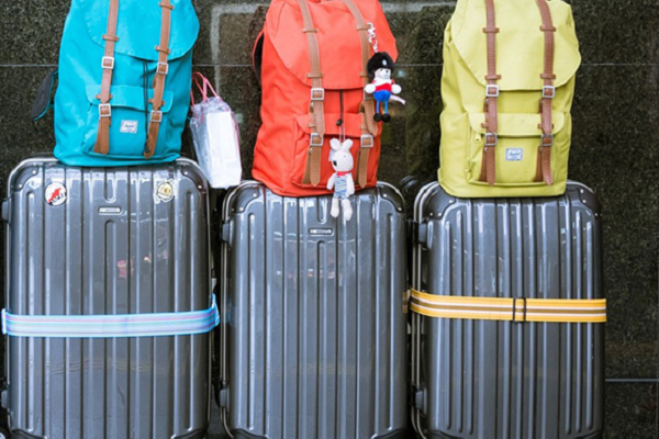 three suitcases along a wall with different coloured backpacks on top