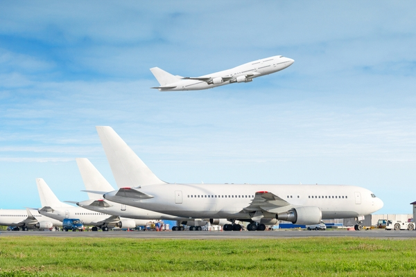 A row of airplanes, with one taking off