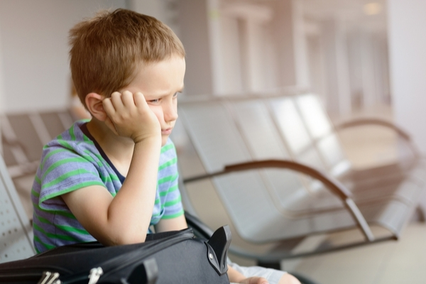 Young boy waits, bored, in an airport