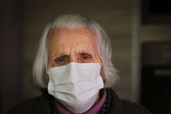 Senior woman wearing a face mask and looking scared