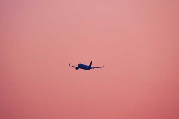 Plane taking off against a pink sky