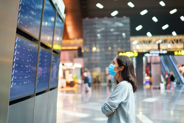 worried woman looking at departures board wearing mask in airport