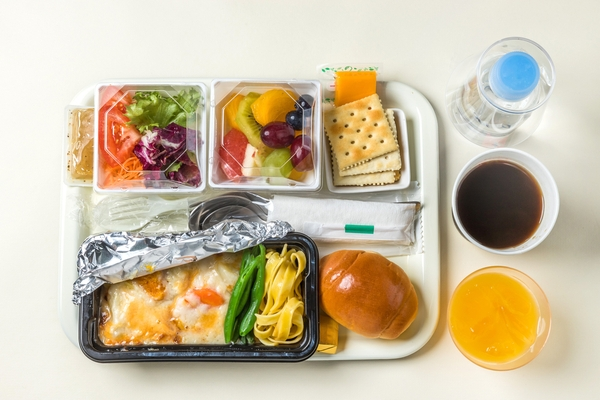 An airline meal served on a plastic tray with plastic cutlery and plastic water bottles and cups