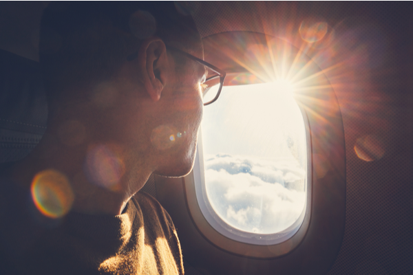 Smiling man looking out airplane window
