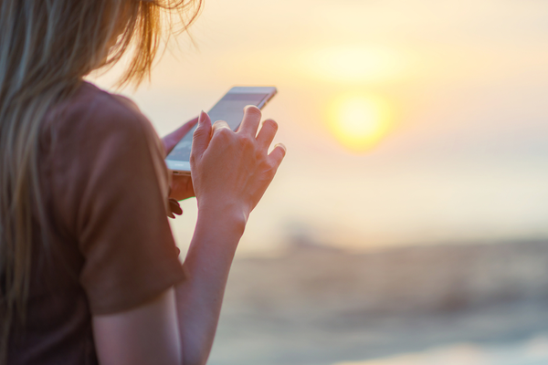 woman on beach looking at phone with sun setting in the background